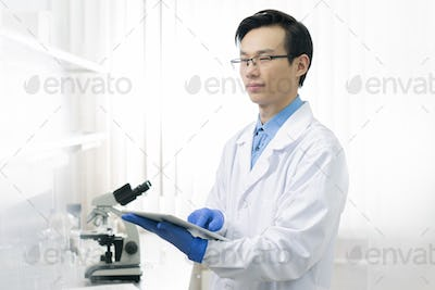 Young scientific researcher in workwear using touchpad to get online information