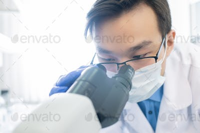 Chinese male scientist looking in microscope during scientific experiment