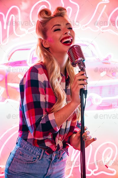 Photo of cheerful caucasian woman with microphone singing and smiling