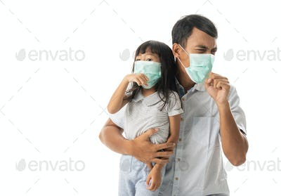 father and daughter wearing face masks coughing