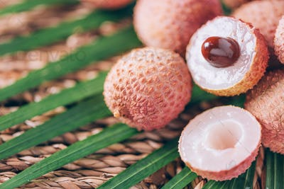 Lychee fruits with palm leaves on rattan background. Copy space. Exotic litchi, lichee fruits