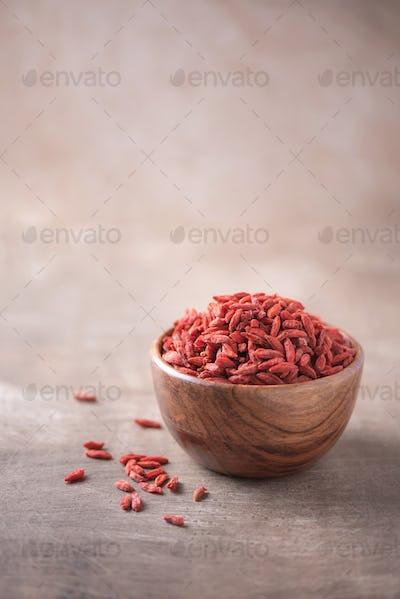 Goji berries in wooden bowl on wood textured background. Copy space. Superfood, vegan, vegetarian