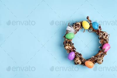Easter willow wreath and colorful Easter eggs on blue background. Top view, copy space