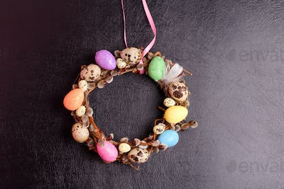 Easter willow wreath and colorful Easter eggs on leather background. Top view, copy space