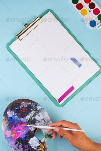 Woman's hand with paintbrush above blank white paper sheet on a light blue background. Flat lay