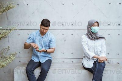 social distancing man using hand sanitizer