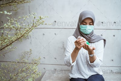 muslim woman using hand sanitizer gel