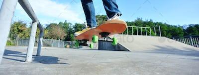 Skateboarder doing a trick ollie on skatepark