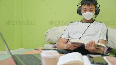 Male student with mask reading a book on the bed to prepare for the exam.