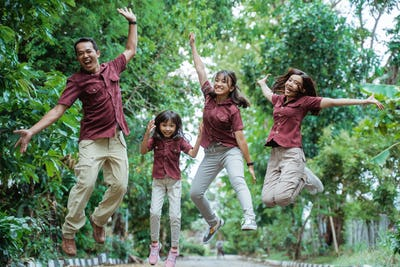 having fun asian family jumping with raised hands