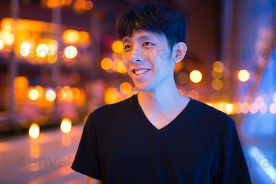 Happy Asian Man Thinking Outdoors At Night