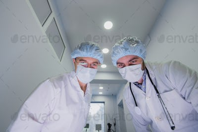 Doctors in a viral protective suit, in a white masks, looks into the camera from above like you as a