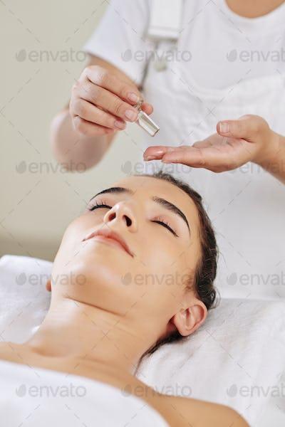Beautician applying massage oil