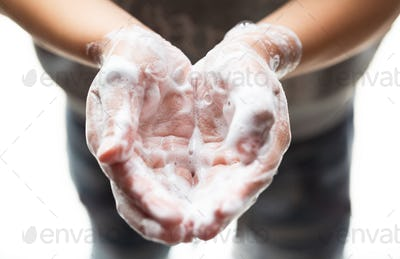 Boy Washing hands with foam soap to be protected against covid