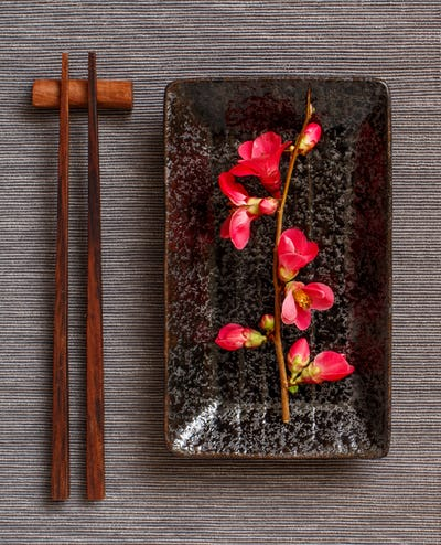 Chopsticks, rectangular plate and pink flowers on gray runner