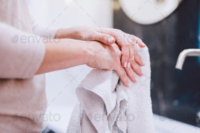 Woman wiping hands in towel after washing them. Hygiene