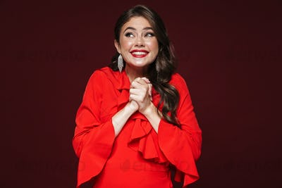 Image of happy woman wearing red dress smiling with looking upward