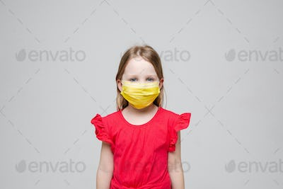 Portrait of little girl with yellow medical mask on her face, isolated on grey background