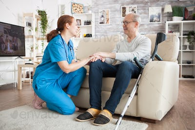 Old man with glasses sitting on couch in nursing room