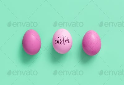 Pink eggs with inscription EASTER over light green background