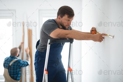 Professional repair team measures the wall before renovation of the living room