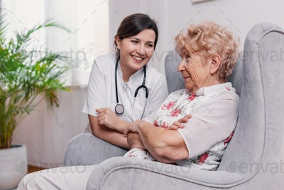 Senior seating on armchair in nursing home and talking to doctor