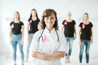 Beautiful female doctor in white uniform with pink bow standing in front of patients