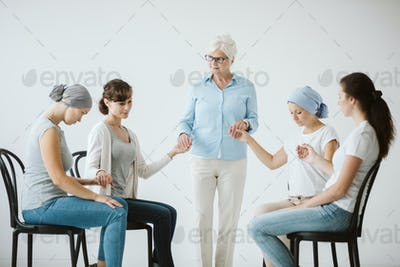 Group of women sitting together during psychotherapy with senior counselor