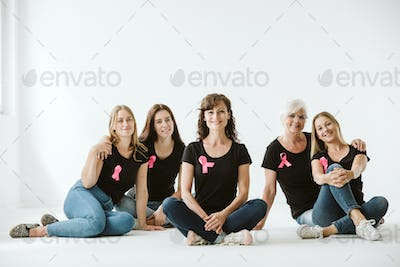 Five women dressed in jeans and black T-shirts with pink bows sitting on the floor of empty interior