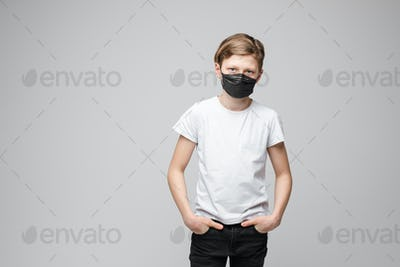 Teenage boy stands in black medical mask, portrait isolated on grey background