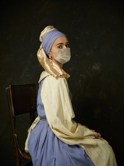 Medieval young woman as a lady with a pearl earring wearing protective face mask against coronavirus