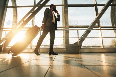 Traveller Talking On Mobile Phone Walking With Suitcase In Airport