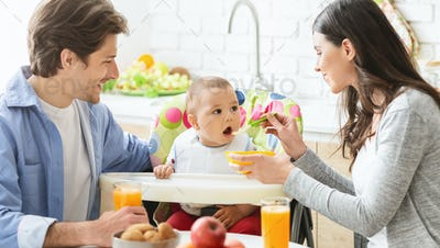 Young mother and father feeding baby son at kitchen