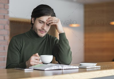 Upset young man sitting at cafe and drinking coffee alone