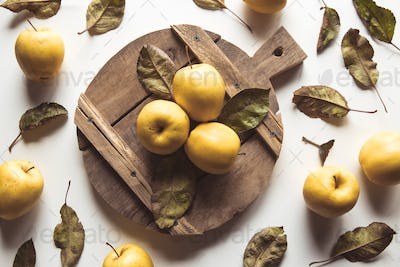 Yellow apples on a sliced board in vintage style. leaves, food, wholesome food, vegan, farm product