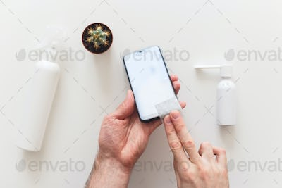 Man disinfects smartphone wiping by antibacterial wipe to prevent yourself from coronavirus COVID-19