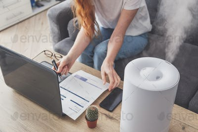 Woman freelancer uses a household humidifier in the workplace to maintain relative humidity