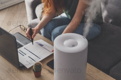 Woman freelancer uses a household humidifier in the workplace at home office with laptop