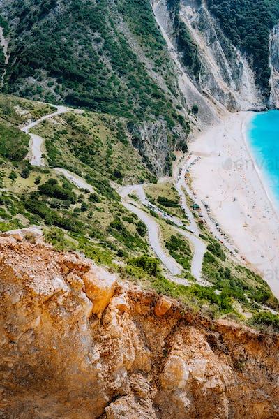 Serpentine zigzag road down to famous Myrtos Beach. Orange rocks ravine on side. Sunny beach from