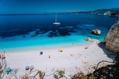 Fteri beach, Cephalonia Kefalonia, Greece. White catamaran yacht in clear deep blue sea water with