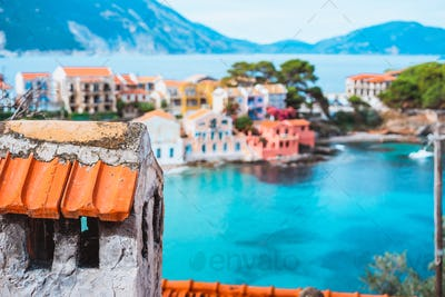 Tile chimney in front of Assos village. Beautiful view to vivid colorful houses near blue turquoise