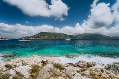 Crystal clear transparent blue turquoise teal Mediterranean sea water in Fiskardo town. White yacht