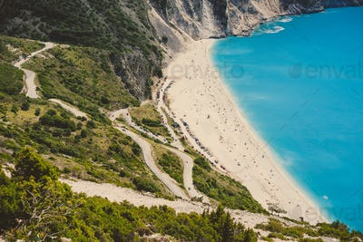 Serpentine road to famous Myrtos Beach with many tourists, Kefalonia, Greece