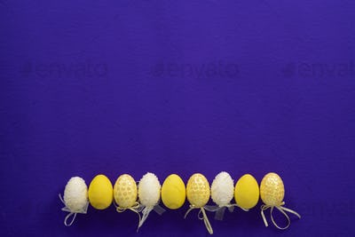 Easter yellow painted decorative eggs on a dark purple background