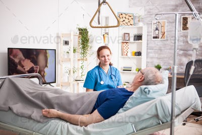 Sick old man laying on bed in nursing home