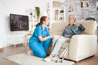 Nurse in knees talking with old woman