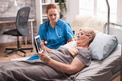 Old woman in nursing home sitting in bed using tablet computer