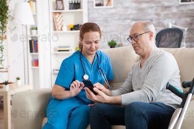 Female doctor in nursing home showing old man