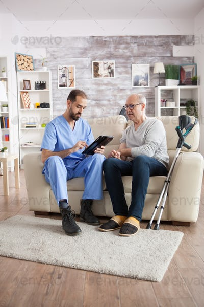 Young male doctor in nursing home taking notes on tablet pc