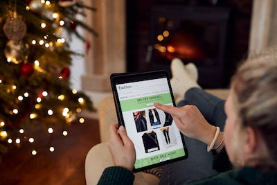 Woman At Home Using Digital Tablet To Shop For Clothes Online At Christmas
